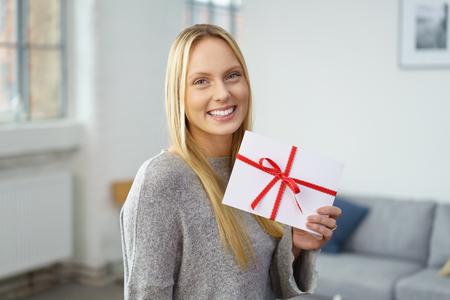 sobres para carta: Orgulloso feliz atractiva mujer rubia joven que sostiene un sobre festivo atado con una cinta roja que muestra a la cámara mientras se encuentra en su sala de estar en casa, imagen conceptual