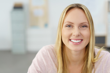 welcoming: Close up Cheerful Young Office Woman, with Long Blond Hair, Smiling at the Camera Against Blurred Workplace.