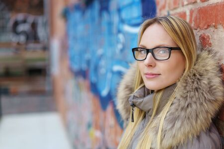 withdrawn: Pretty Woman Wearing Eyeglasses and Winter Jacket Leaning Against Brick Wall and Looking at the Camera.