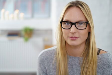 Serious thoughtful young woman with long blond hair wearing glasses looking pensively at the camera, blurred indoor home background with copy-space