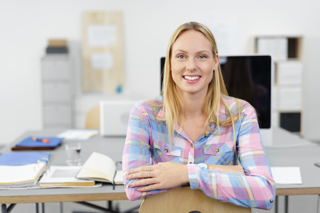 smiling young businesswoman sitting on a chair with arms folded Stock Photo