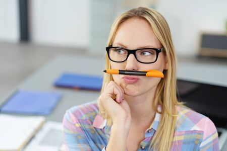 personal assistant: Close up Thoughtful Young Office Woman Balancing her Pen Between her Nose and Lips While Looking Away.