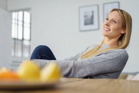 aire puro: Feliz mujer joven magnífica que se sienta en casa soñando despierto mirando hacia arriba en el aire con una expresión lejana y una sonrisa de placer, bajo ángulo de vista sobre la mesa de comedor y fruta fresca