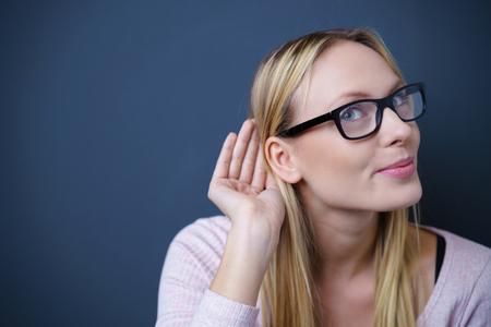personas escuchando: Cierre de la mujer bonita joven que escucha algo en contra de Dark Blue Gray pared con espacio de copia. Foto de archivo