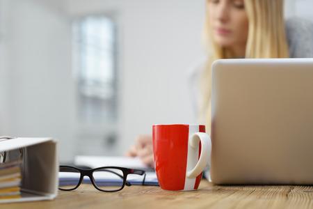 tomando café: mujer estudiante que trabaja en casa con una taza de café roja y anteojos sobre la mesa