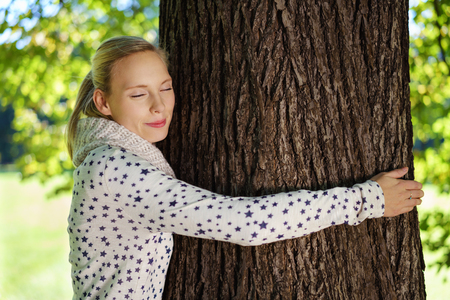 Close up Thoughtful Young Woman Hugging a Big Tree Trunk at the Park with Eyes Closed. Stock Photo