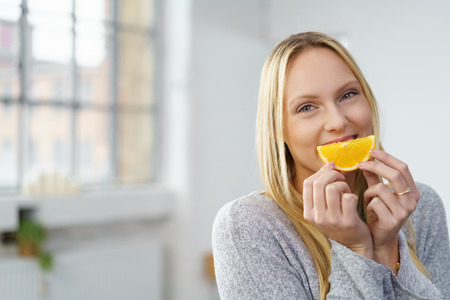 covering: healthy young woman sitting in a bright white room eating a piece of an orange