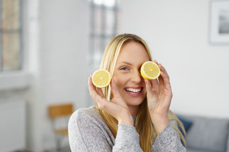 Laughing vivacious attractive young blond woman holding a cut halved fresh lemon to her eye as she relaxes at home in a conceptual image Foto de archivo