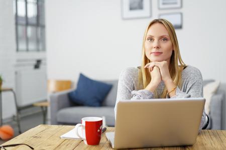 pewni, młoda kobieta siedzi w domu z jej laptopa za brodę na dłoniach Zdjęcie Seryjne