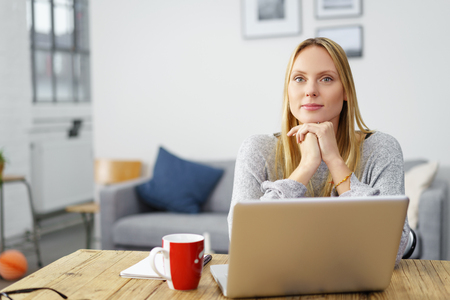 confident young woman sitting at home with her notebook with her chin on her hands