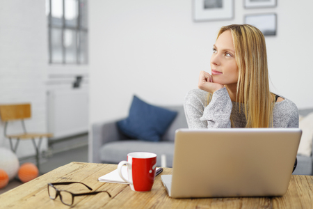 young blond woman working on her laptop at home looking to a side in thoughts