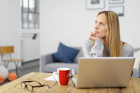jovem mulher loira trabalhando em seu laptop em casa olhando para um lado em pensamentos