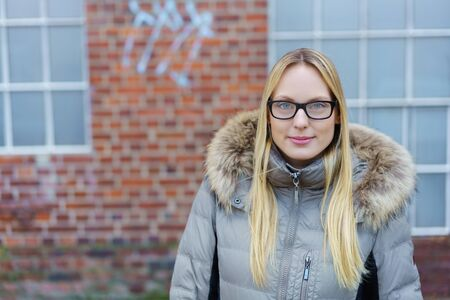 parka: beautiful young woman with glasses going for a walk in the city