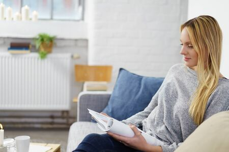 Attractive young woman unwinding at home relaxing on a sofa reading a magazine with a quiet smile of pleasure, side view