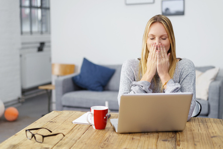 mistake: woman sitting at laptop at home holding her hands on her mouth afraid of a computer virus or a mistake
