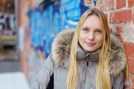 anorak: modern woman leaning against a brick wall with blue graffiti in background