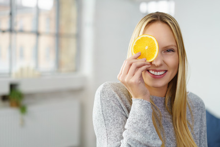 healthy woman holding a piece of an orange in front of her eyes and smiling at the camera
