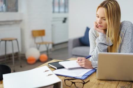 молодая блондинка делает документы, сидя за деревянным столом в своей квартире