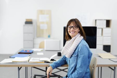denim jeans: smiling businesswoman with glasses at workplace smiling at the camera Stock Photo