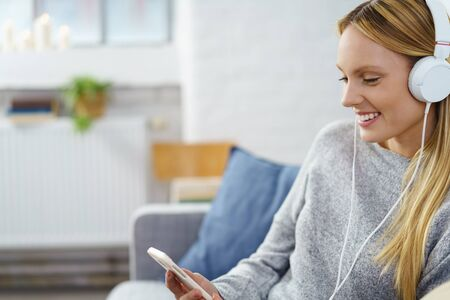 tunes: Young woman enjoying her music as she relaxes on a sofa at home listening to tunes on her mobile phone with a happy smile