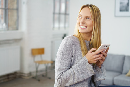 stijlvolle vrouw met behulp van haar mobiele telefoon als ze zit in haar appartement Stockfoto