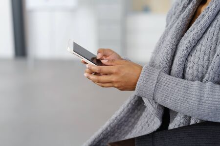 ethnic woman: Young businesswoman sending text messages on her mobile phone, close up of her hands and the cellphone Stock Photo