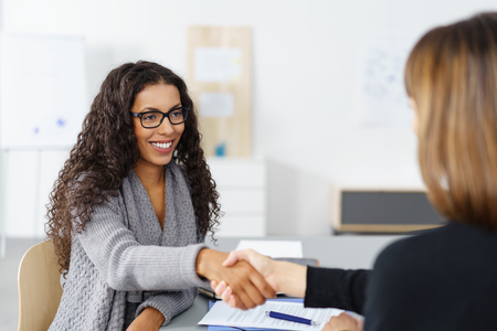 transaction: Two businesswomen shaking hands over a desk as they close a deal or partnership, focus to a smiling young African American lady Stock Photo