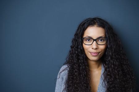 confianza: mujer segura con gafas mirando a la cámara de pie contra el fondo gris oscuro en el estudio