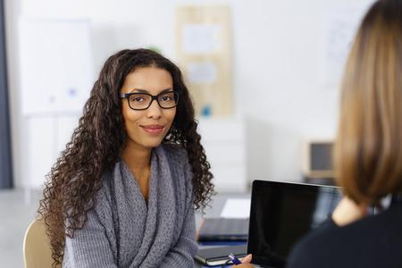 mujer de negocios en una reunión sonriendo a la cámara