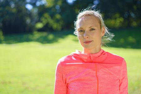 tracksuit: Healthy young woman in a colorful pink tracksuit standing looking at the camera outdoors in a park in an active lifestyle and wellness concept, with copy space