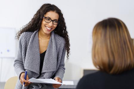 Sonriendo empresaria afroamericana en una reunión con un colega, que hablarán de un documento conjunto