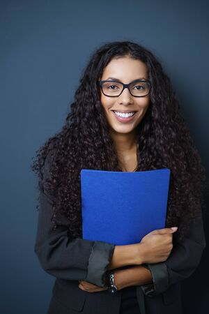 seeker: Motivated young African American job seeker clutching a blue CV in her hands standing against a blue background beaming at the camera