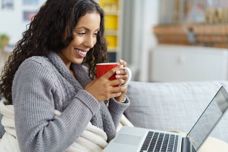 african american woman snuggling into a warm blanket while sitting on her sofa with her laptop and a cup of coffee
