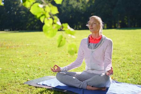 éxtasis: Serene practicar yoga mujer joven sentada en una colchoneta en el parque en la posición de loto meditando en un concepto de bienestar