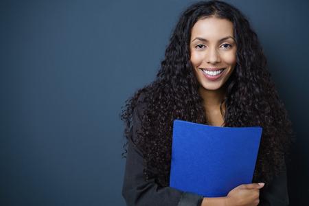 puesto de trabajo: Motivado joven demandante de empleo afroamericana agarrando un CV azul en las manos de pie sobre un fondo azul con copia espacio sonriendo a la cámara