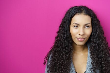 american content: portrait of an attractive young woman smiling with a faraway expression against pink background
