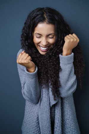 Jubilant vivacious young African American woman cheering in excitement as she clenches her fists, against a dark studio background