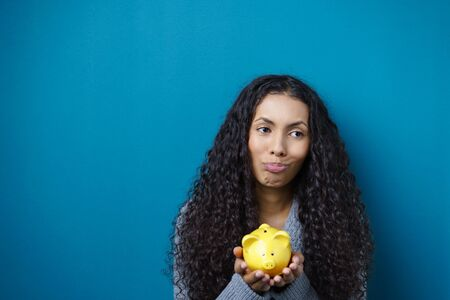 wry: Wry young African American woman holding a yellow ceramic piggy bank in her hands with a grimace to show she has been unsuccessful at saving her money, with copy space