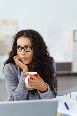 introspective: Thoughtful businesswoman sitting as her desk enjoying a mug of hot coffee and looking off to the side with a pensive expression