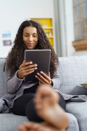 attractive couch: Young woman using tablet sitting barefooot on the sofa
