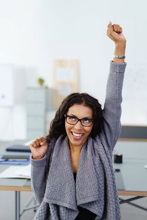 Excited young business woman stretching her arms up laughing in jubilation at her success