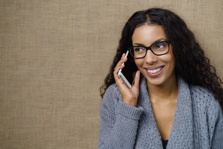 amigas conversando: Joven mujer afroamericana que charla en un teléfono móvil escuchando la conversación con una sonrisa, fondo marrón con espacio de copia