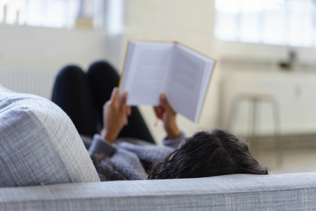 american content: woman lying on her sofa reading a book, view over the shoulder Stock Photo