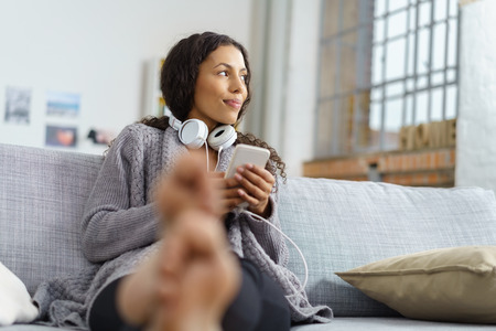 woman relaxing: woman relaxing in her living room and looking out of the window while listening to music on her smartphone Stock Photo