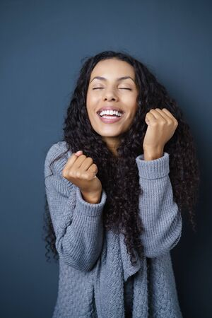 jubilation: Excited attractive young African American woman cheering and clenching her fists in jubilation, dark studio background