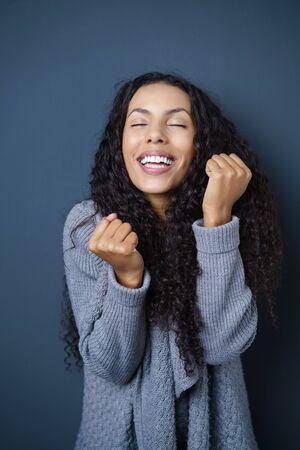 Excited attraktive junge African American Frau jubeln und ihre Fäuste in Jubel, dunklen Studio-Hintergrund ballte Standard-Bild