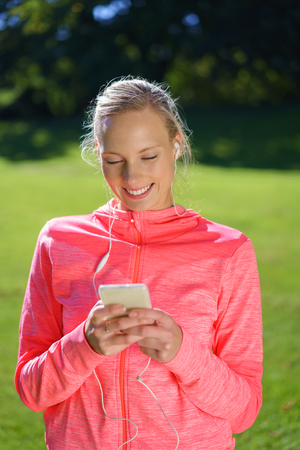 selects: Pretty young woman enjoying her music outdoors standing in a park in her sportswear smiling as she selects a tune from the library on her mobile phone