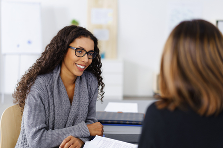 woman in office: Attractive young African American businesswoman wearing glasses in an interview with a female manageress listening attentively to the questions Stock Photo