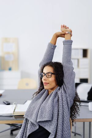 Young African American businesswoman stretching her arms in the air to relieve tension and stress with a look of peaceful bliss