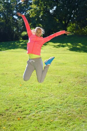 Joyful agile young woman leaping in the air with outstretched arms as she enjoys a sunny day out in a lush green park, with copy space below